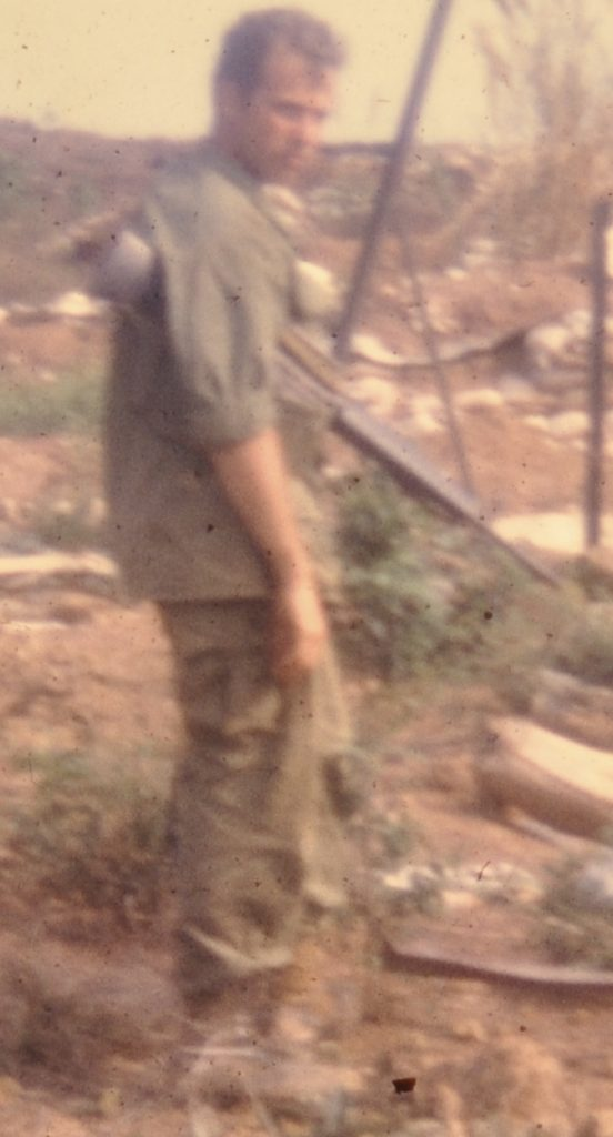 A blurry photo of 1st Lieutenant Dave Anson carrying his weapon at Lang Vei just before his unit is overrun in April 1969.