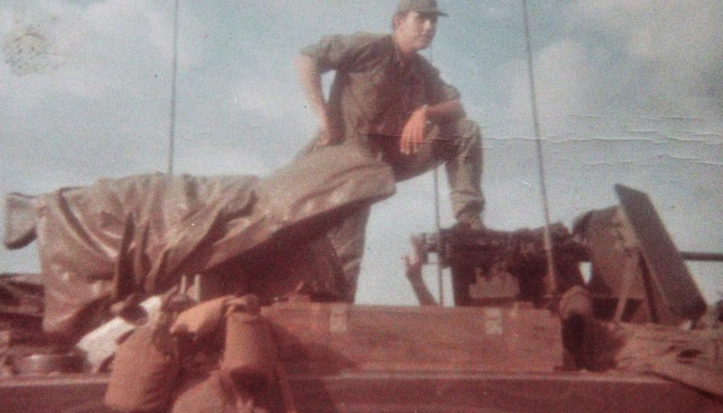 1st Lieutenant Dave Anson standing on top of an armored vehicle in Vietnam.