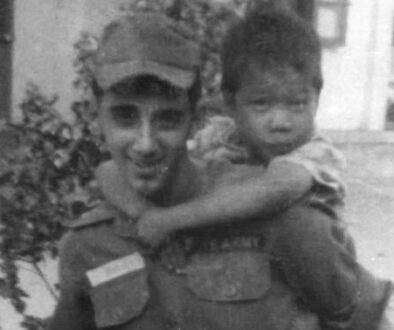 Specialist Billy Terrell at Mang Lang Orphanage with a boy on his back