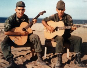 Image of 2d Lt Jordan Klempner and Billy playing guitar on the beach at Tuy Hoa in 1967